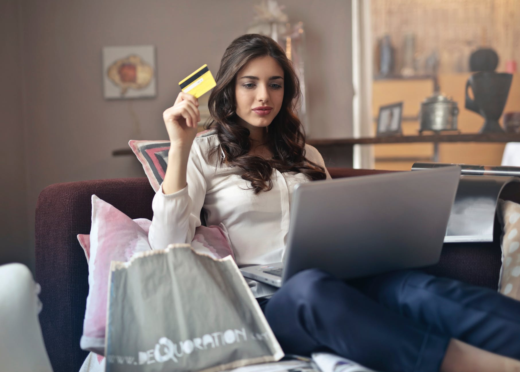 Young woman shopping online, holding her credit card ready to pay.